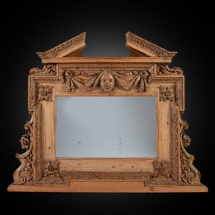 A George II pine overmantel mirror in the manner of William Kent, the richly carved baroque frame with broken pediment above a swag hung mask, the mirror frame throughout profusely detailed with carving in high relief of foliate details and swags of plentiful flowers.