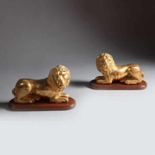 Empire period Sicilian giltwood models of couchant lions