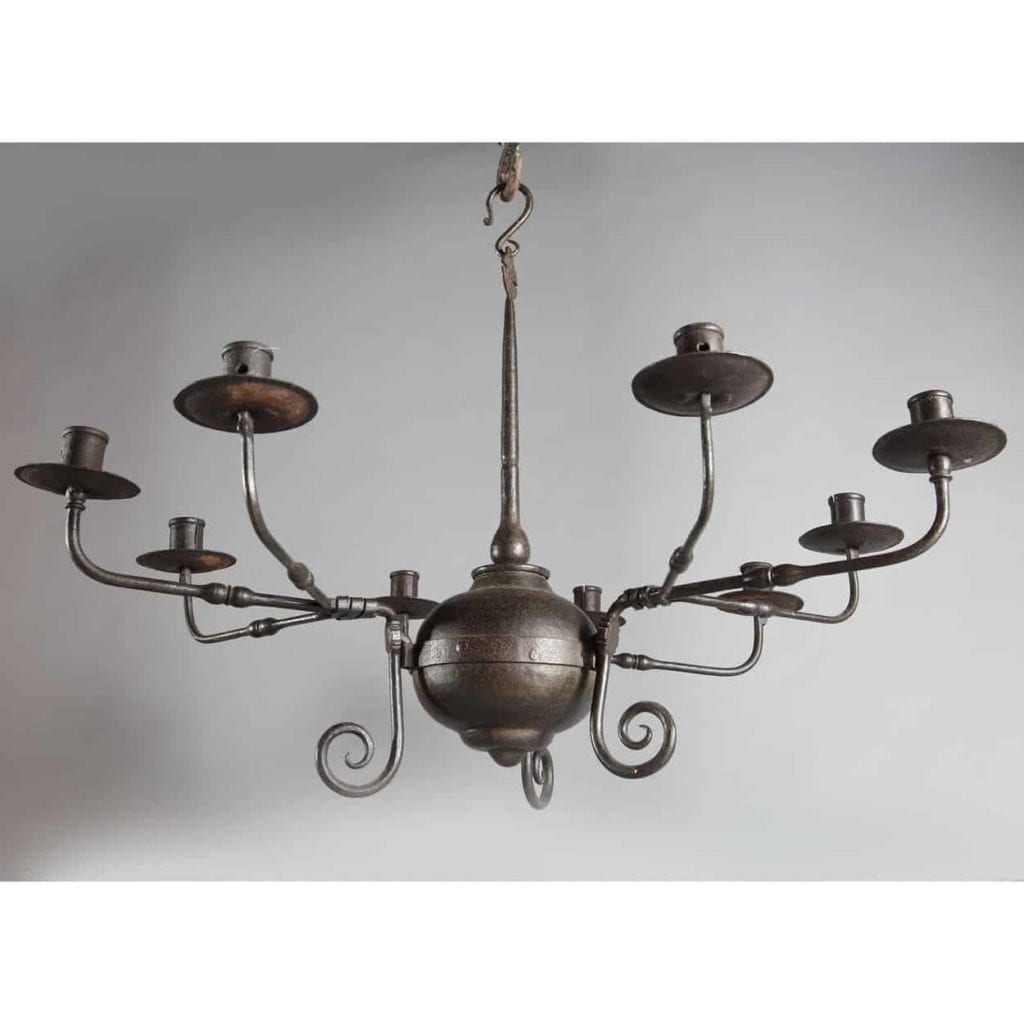 An Arts and Crafts black patinated nine branch Iron chandelier. The branches hook on a cluster of three and terminate in scrolls. The central stem finishes in a slightly oriental flattened pierced disk. England circa 1880 Height 30 ins, diameter 24 ins.