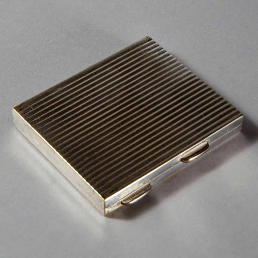 A vintage ribbed silver plate ladies compact fitted with its original bevelled mirror plate.