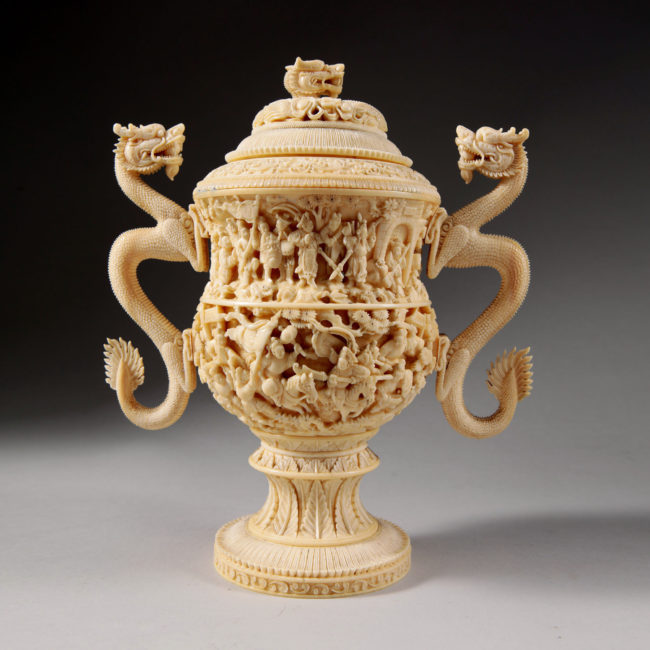 A carved ivory cup and cover with dragon-handles and figures in relief, China, Qing Dynasty, 19th century