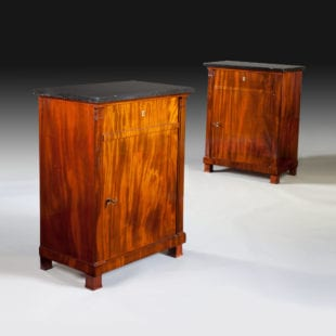 A very fine and rare pair of French Empire period cabinets in highly figured Cuban mahogany. Both cabinets opening to cupboard space and one with a additional fall front opening to a sliding writing surface retaining its original tooled leather surface and two oak drawers. Both cabinets retaining their original keys, one with a shamrock cylinder and the other with a double cylinder. With black marble tops.