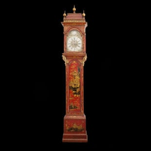 A magnificent large scale red lacquer Queen Anne longcase clock. Having exceptional lacquer and unusual finely carved brackets below the hood. The movement by Austin of Shoreditch. England circa 1720.