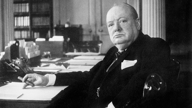 Sir Winston Churchill - Seated with a lit Dunhill Aquarium Table Lighter at his Desk in Chartwell