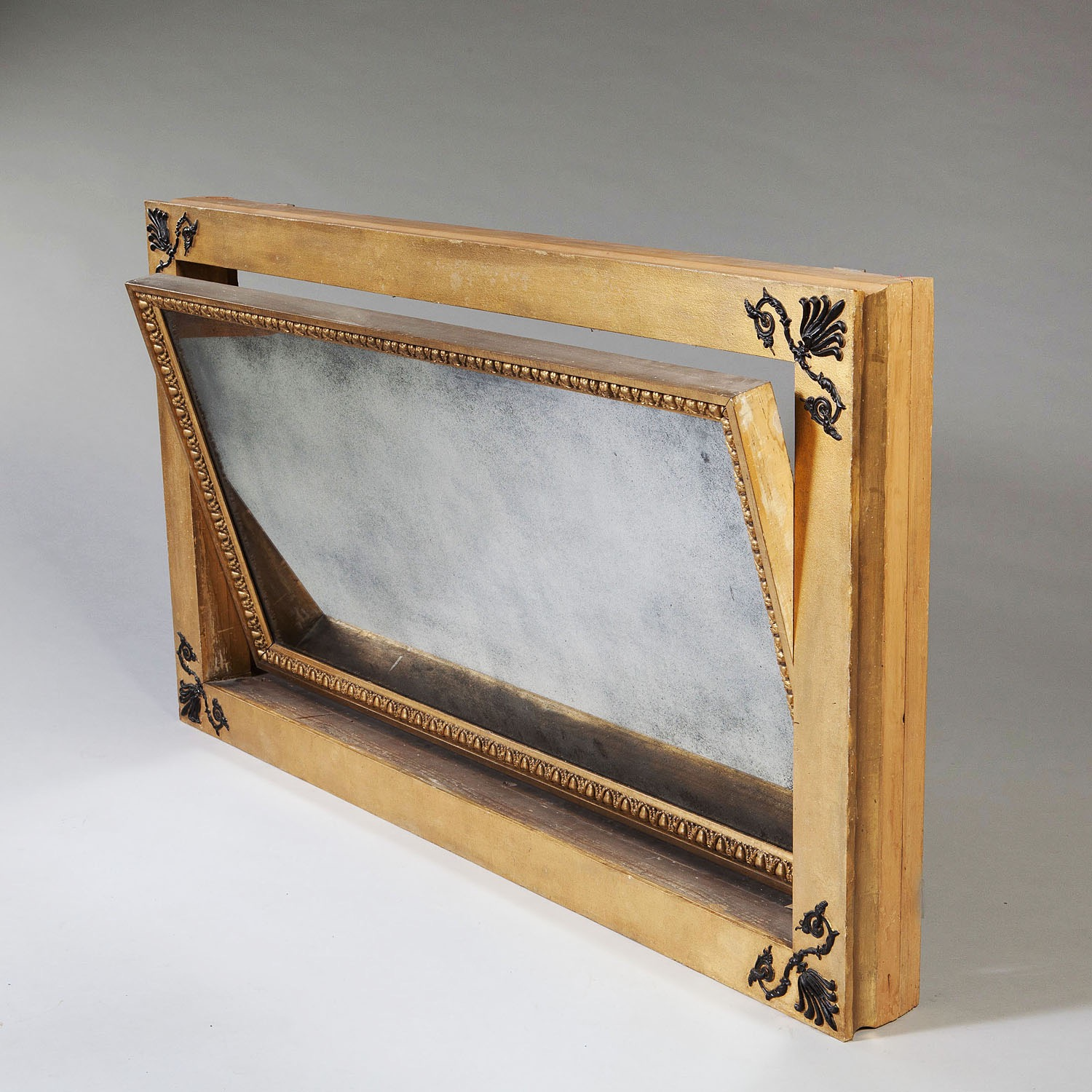 A rare and unusual Regency parcel gilt mechanical patent overmantel mirror. The reverse bears the trade label'Freeman, carver, gilder, and looking glass manufacturer of London and Swan Lane, Norwich'.