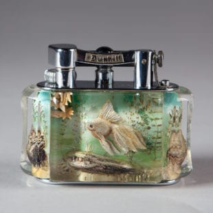 England 1955A very fine Dunhill Aquarium Table Lighter, the top with raisable arm stamped Dunhill and Reg. No 737418 on the reverse, above the lucite body carved with tropical fish scenes. The panels are all well composed and colourful. The metal mounts are all chrome plated. The base stamped DUNHILL LIGHTER 'Made in England'Length 4in 10cm
