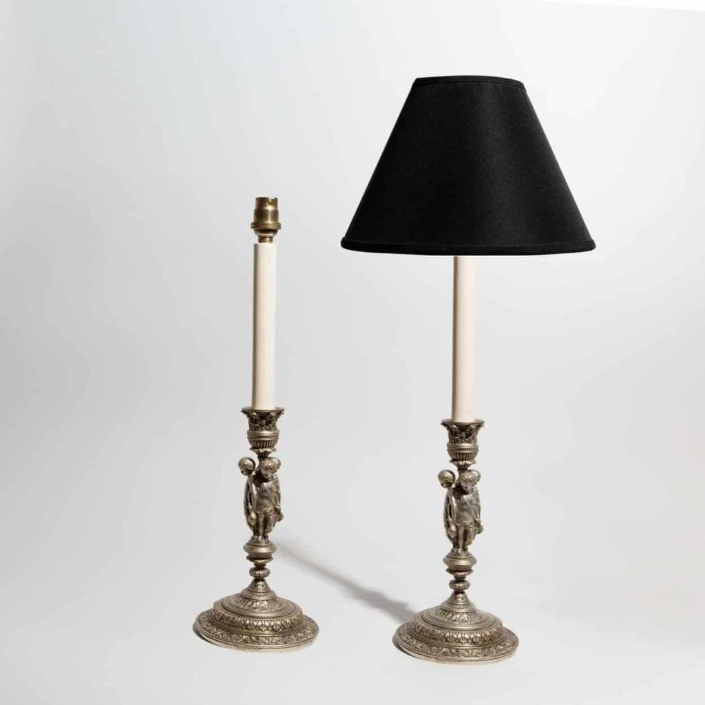 Antique Table Lamps - Pair of 19th century Renaissance revival candlesticks in the form of three putti below a foliate nozzle and above a stepped circular base with leaf ornament.