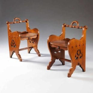A pair of oak arts and crafts back stools, with boldly fashioned carrying handles above multiple scrolling elements, the sides pierced with a trefoil element. In the manner of Richard Bridgens. England circa 1870.